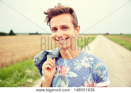 nature, summer, youth culture and people concept - smiling young hippie man on country road chewing rye spike