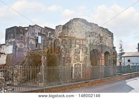 The archaeological site contains the ruins of the Roman Odeon built of the local black lava rock and surrounded by residential buildings Catania Sicily Italy.