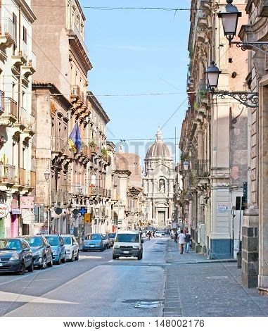 CATANIA ITALY - OCTOBER 10 2012: The old street of Giuseppe Garibaldi with high old buildings leads to the Duomo Square with St Agatha Cathedral on background on October 10 in Catania.