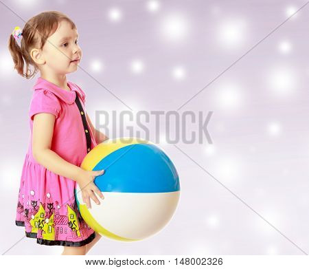 Beautiful little girl in a pink dress throwing a big striped ball. Turned sideways. Close-up.On new year's or Christmas purple background where glowing large white star.