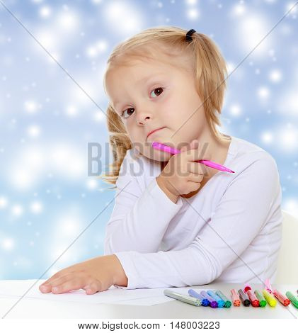 Pretty little blonde girl drawing with markers at the table.The girl thoughtfully looks into the camera.The concept of celebrating the New year, Holy Christmas, or child's birthday on a blue