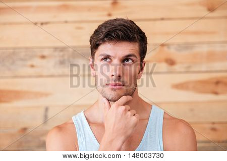 Portrait of a pensive man touching his chin isolated on a wooden background