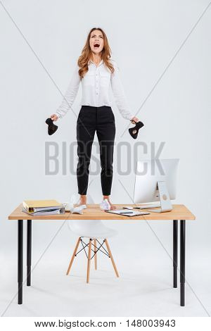 Full length of mad young businesswoman standing on table and shouting over white background