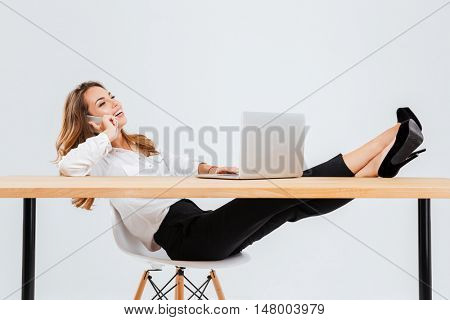 Cheerful young businesswoman using laptop and talking on cell phone with legs on table over white background