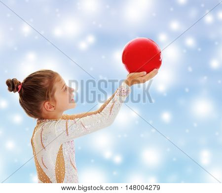 Cute little girl gymnast turned sideways to the camera , holding in his outstretched hands a red ball.On a blue background with large, white, Christmas or new year's snowflakes.