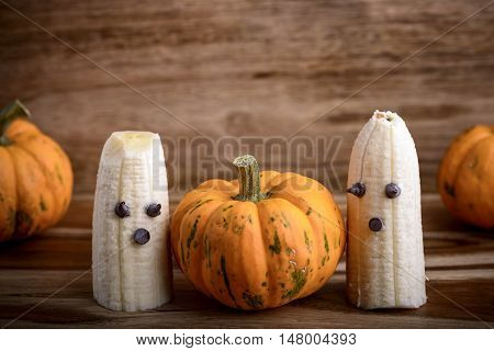 Three pumpkins and ghosts made with banana and chocolate for halloween over wood