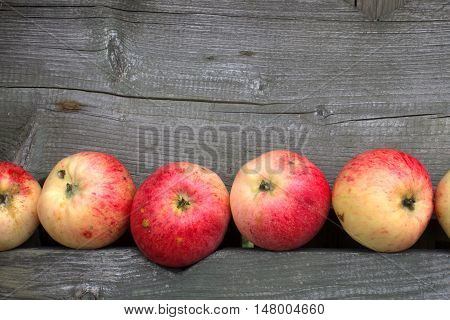 Sweet juicy fresh red apples on the old gray wooden table. Wooden Rustic melancholic autumn backdrop