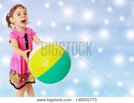 Emotional little girl with pigtails on the head , in a pink dress. Girl catches with hands a large, inflatable striped ball.On new year or Christmas blue background with white big stars.