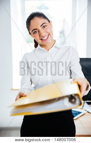 Happy smiling businesswoman giving yellow folder and looking at camera at the office