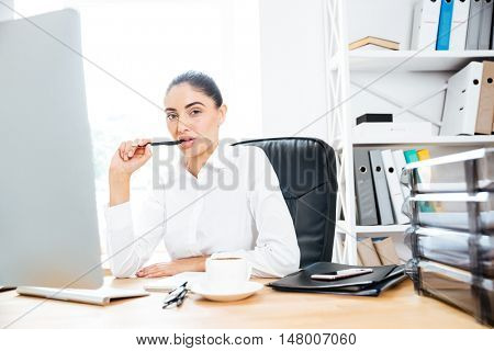 Attractive charming businesswoman sitting at her workplace holding pen and looking at camera