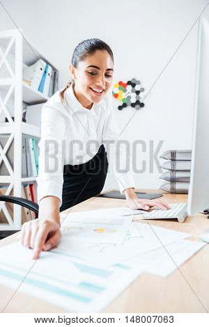 Happy beautiful businesswoman pointing finger at graphic report laying on the desk at office