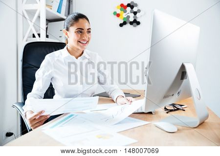 Smiling happy businesswoman holding reports and looking at computer while sitting at the workplace
