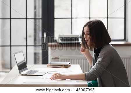 Attractive business woman reading paperwork at office. Successful businesswoman, leadership, bureaucracy concept