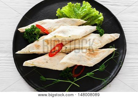 Rolls of bread lavash filled with red sweet paprika, herbs and lettuce, flat lay