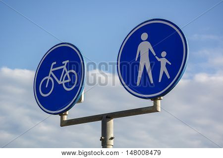Blue signpost for people and bikes with blue sky as background