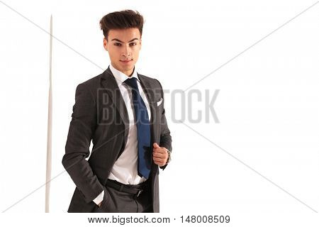 smiling business man with hand in pocket looks at the camera, with copy space on white background