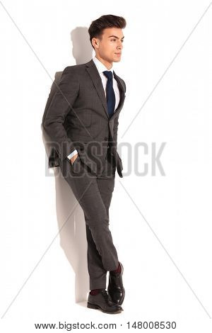 full body picture of young business man with hands in pockets and legs crossed looking away from the camera on white background