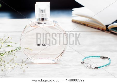 Ukraine, Kharkiv - 05.08.2016 - Chance Eau Vive Chanel perfume on white wooden table with female diary and accessories. Chanel is fashion house, specializes in luxury clothes and fashion accessories