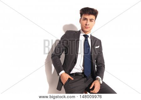young business man sitting on chair with one hand in pocket on white background with copyspce