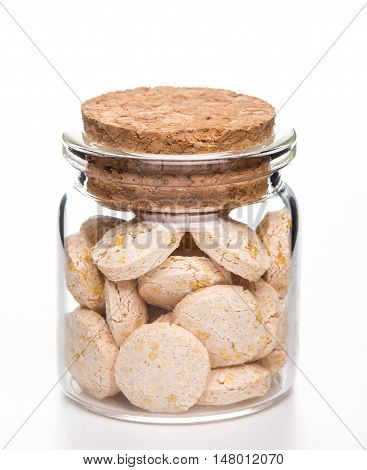 Decaying pills medicine in glass container and white background
