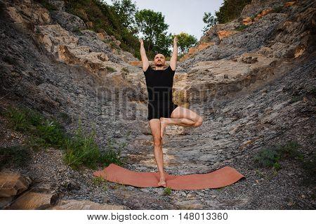 Athletic Man doing Yoga on the Rocks tree pose