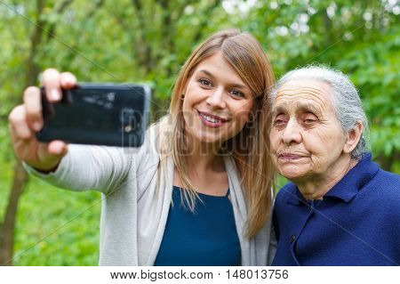 Picture of a beautiful young woman taking selfies woth her grandmother