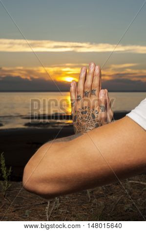 Closeup of male hands with tattoos in meditation position. young man practicing yoga outdoors.