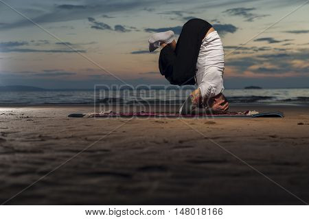 Young flexible man with tattoos doing high level yoga asana on the beach at sunset. Head stand exercise.