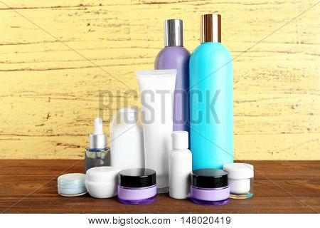 Different cosmetic bottles on yellow wall background