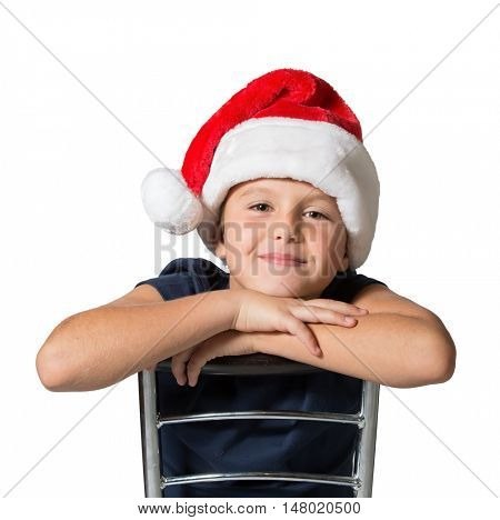 Charming seven year old boy in red Santa Claus hat cheerfully smiles. Photo executed on a white background