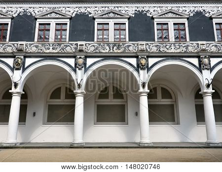 White arcade of old Stables Courtyard with black sculptures of horned animals front view. Dresden, Altstadt Saxony, Germany.
