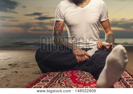 Cropped shot of Flexible tattoo man sitting on the beach and doing stretching exercises. Yoga practice lotus pose.