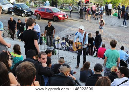 PARIS, FRANCE - MAY 12, 2015: Multi-step staircase to the Sacré-Coeur Basilica is one of the favorite places for performances of street artists. Here is one of those performances.