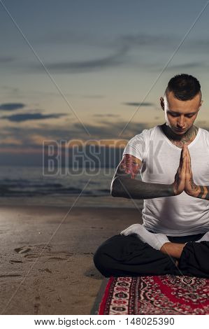 Cropped shot of young man with tattoos on body sitting on the beach at sunset and meditating. Advanced yoga practice, lotus pose.