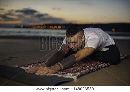 Yoga practice outdoors: flexible young man stretching hands in lotus pose on the beach at sunset