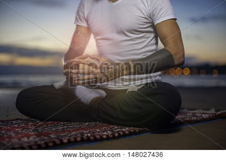 Cropped shot of man practicing yoga on the beach at sunset. Man sitting in lotus position and meditating