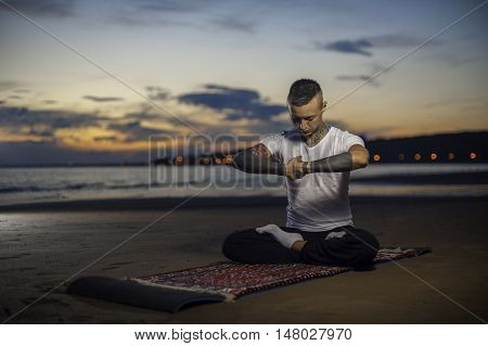 Young caucasian man with tattoos on body sitting on the beach and meditating on lotus position. yoga practice outdoors.
