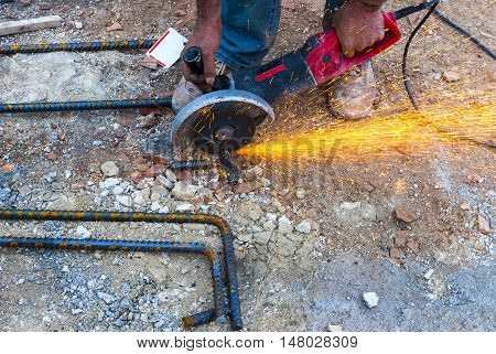 Construction worker cuts rebar circular saw on site.