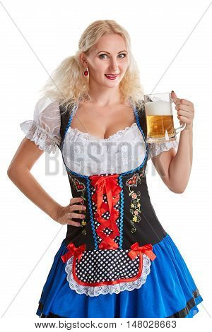 Beautiful young blond girl in dirndl drinks out of oktoberfest beer stein. Isolated on white background. she holds a glass with a drink and smiling