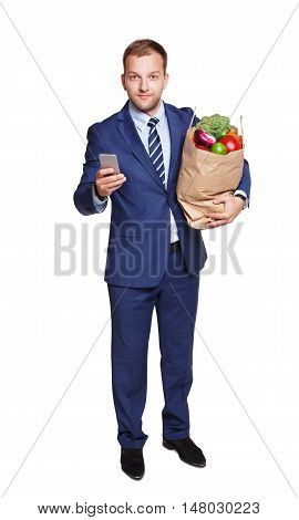Smiling young businessman with mobile phone and shopping paper bag with groceries, vegetables and fruits, isolated at white background. Healthy food shopping. Full length portrait of buyer