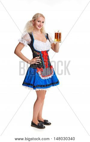 Beautiful young blond girl in dirndl drinks out of oktoberfest beer stein. Isolated on white background. she holds a glass with a drink and smiling. full height