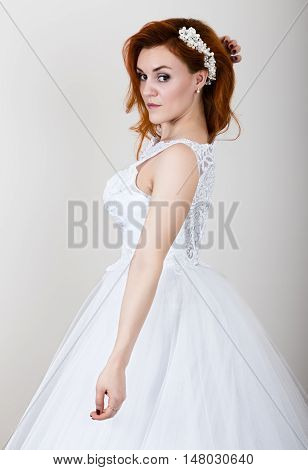 red-haired bride in a wedding dress, bright unusual appearance. Beautiful wedding hairstyle and bright make-up.