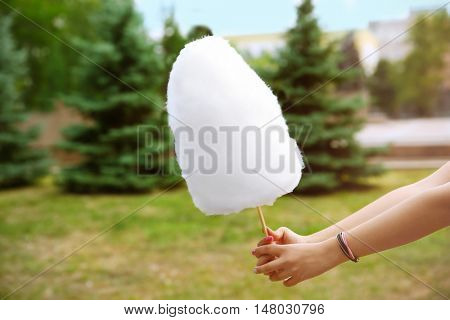 Female hand holding cotton candy outdoors