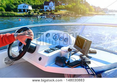 Captain's Hand On Steering Wheel Of Motor Boat