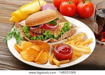 Tasty cheeseburger with fries and ketchup, closeup