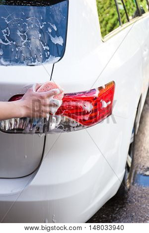 Hand Washing Rear Lights Of Car With Sponge
