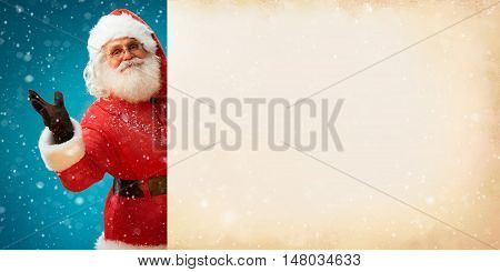 Smiling Santa Claus holding old paper banner with space for Your Text. Merry Christmas & New Year's Eve concept. Close up on blurred blue background.