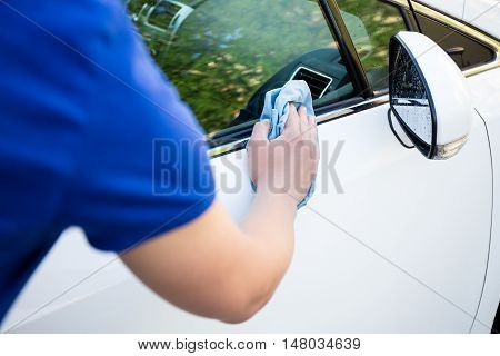 Back View Of Man Cleaning Car With Microfiber Cloth