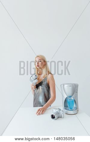 Beautiful young fashion blonde woman pointing blaster at camera while standing at the table isolated on the grey background