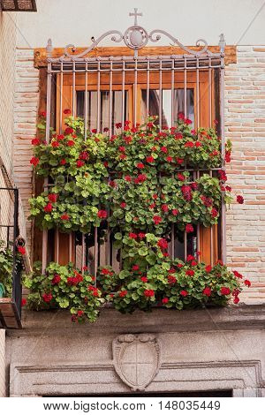 Toledo (Castilla-La Mancha Spain): old typical building in the historic city; window with plants and flowers
